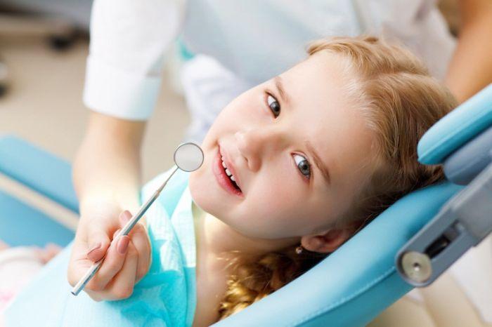 Портрет симпатичной русой девочки на приёме у стоматолога